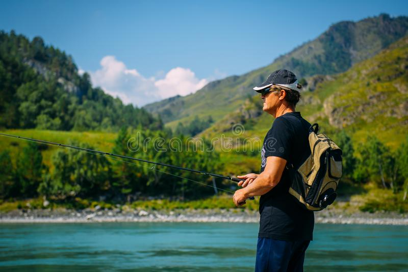 Fisherman on the mountain river at the nice summer day. Trout fly fishing in the mountain river with mountains in background. Altay, Siberia royalty free stock photo