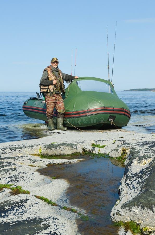 Fisherman near the boat stock image