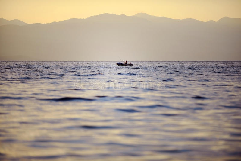 Fisherman on Ohrid Lake at sunset. OHRID, MACEDONIA - AUGUST 18: A man in a fishing boat alone on Ohrid Lake at sunset, on August 18, 2015 in Macedonia stock images