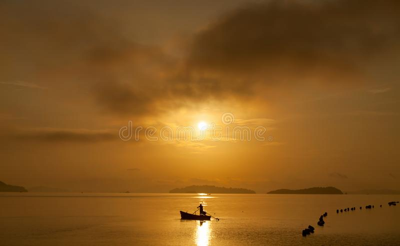 Fisherman with a paddle in small boat at the tropical sea with b. Eautiful sunrise or sunset in phuket thailand royalty free stock photos
