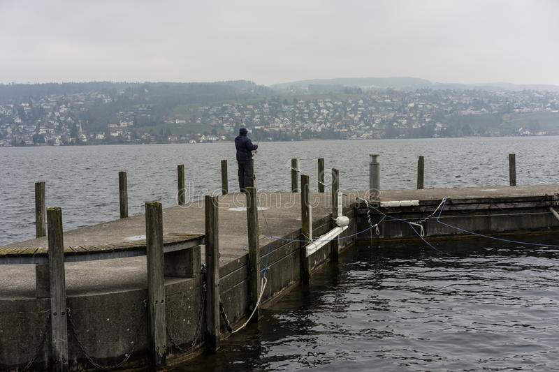 Fisherman on pier in winter on a rainy day stock photo