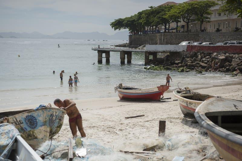 Fisherman prepares a boat, citizens bathe. Copacabana Fort royalty free stock photography