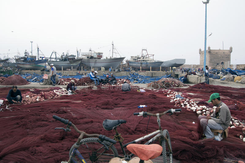 Fisherman prepares his fishing nets. Essaouira Morocco stock photos