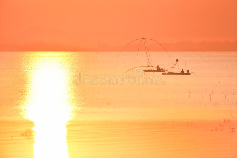 Fisherman with Raft Dip Net at sunset time. Glistening in the la. Ke. Summer season. Silhouette. Warm tone. Thailand stock image