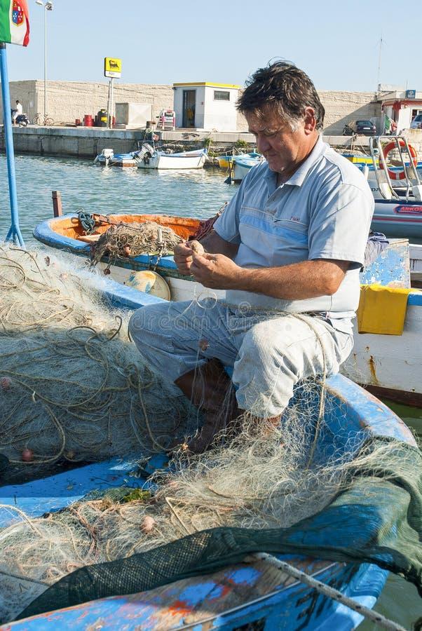 Fisherman repairing fishing nets royalty free stock photos