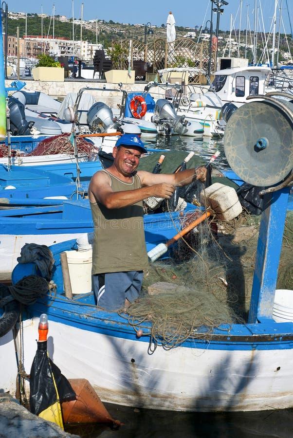Fisherman repairing fishing nets stock photography