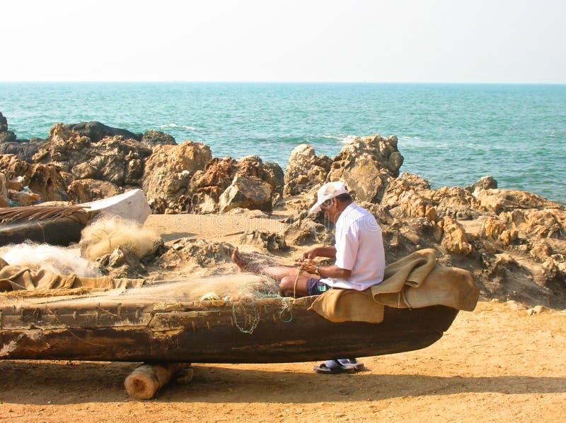 Fisherman repairs his fishing net stock images