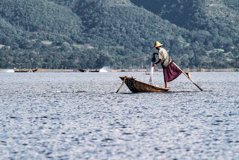 Fisherman rowing boat by leg on Inle Lake, Myanmar stock photography