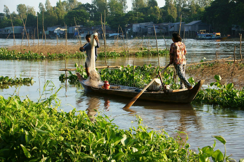 Fisherman rowing row boat to catch fish on river stock images