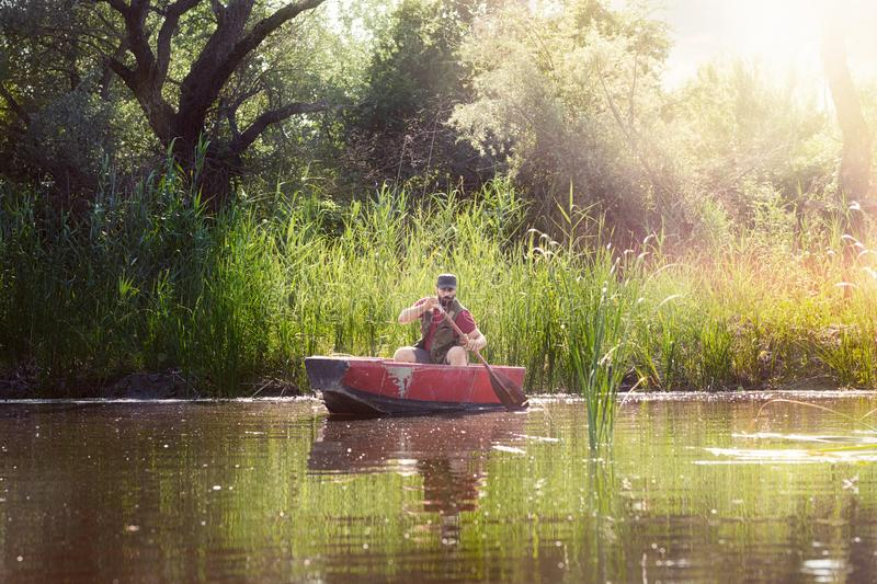 fisherman rowing in a wooden boat royalty free stock photography