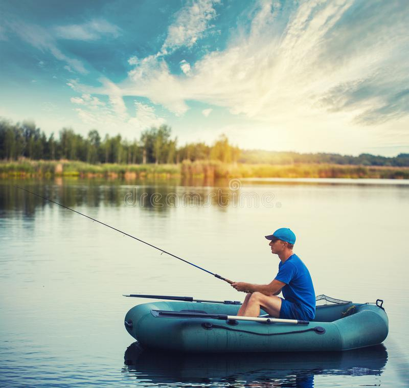 A fisherman in a rubber boat is fishing on the lake stock photos