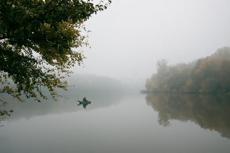 Fisherman in a rubber boat fishing with rods on a small lake, still water surface, reflection, deep fog on a cold autumn morning. Fisherman in a rubber boat stock images