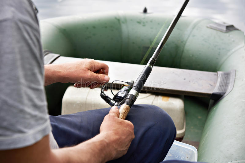 Fisherman`s arms with spinning reel in boat stock photos