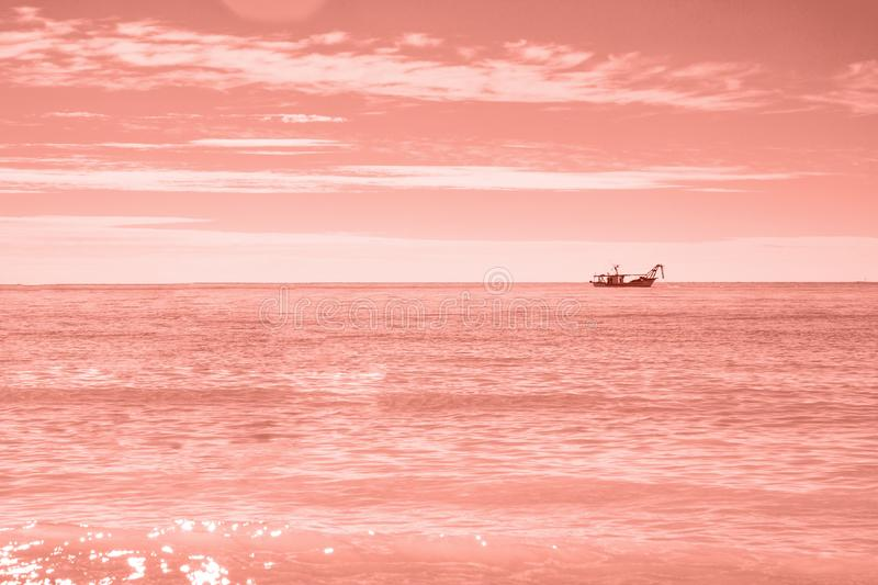 Fisherman's boat in open sea waters at morning to sunrise royalty free stock image