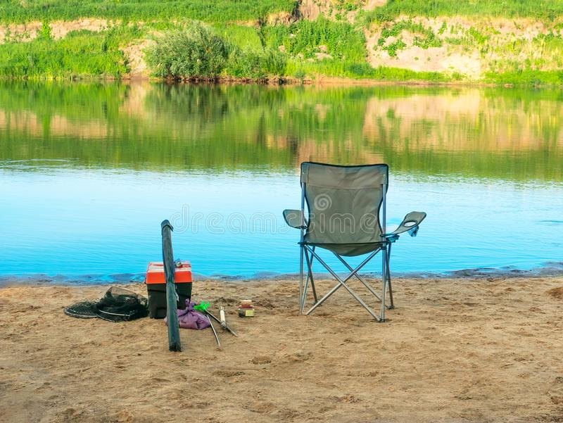 Fisherman`s chair and fishing equipment on sand river coast at summertime, tranquil hobby for summer relax in vacation royalty free stock image