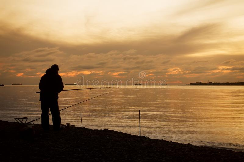Fisherman on a sea coast and majestic sunset over water. royalty free stock image