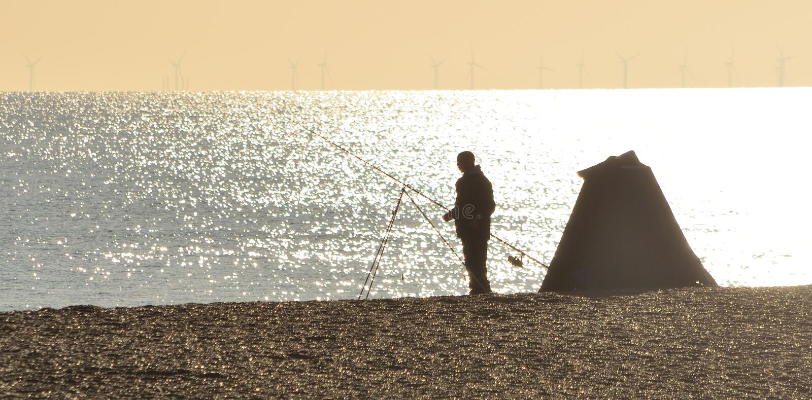 Fisherman Sea Fishing from the Beach royalty free stock photography