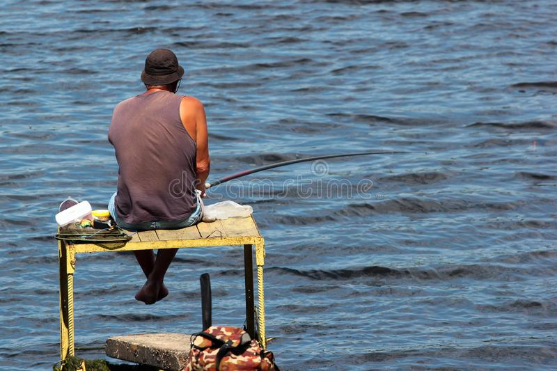 Fisherman on a self-made platform with fishing tackle and rods stock image
