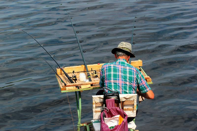 Fisherman on a self-made platform with fishing tackle and rods stock photography