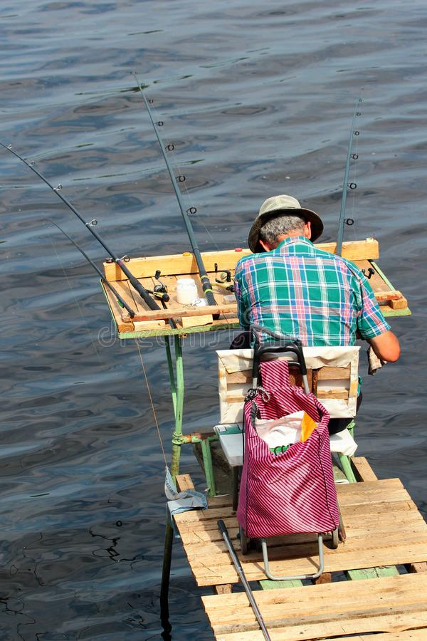 Fisherman on a self-made platform with fishing tackle and rods stock photo
