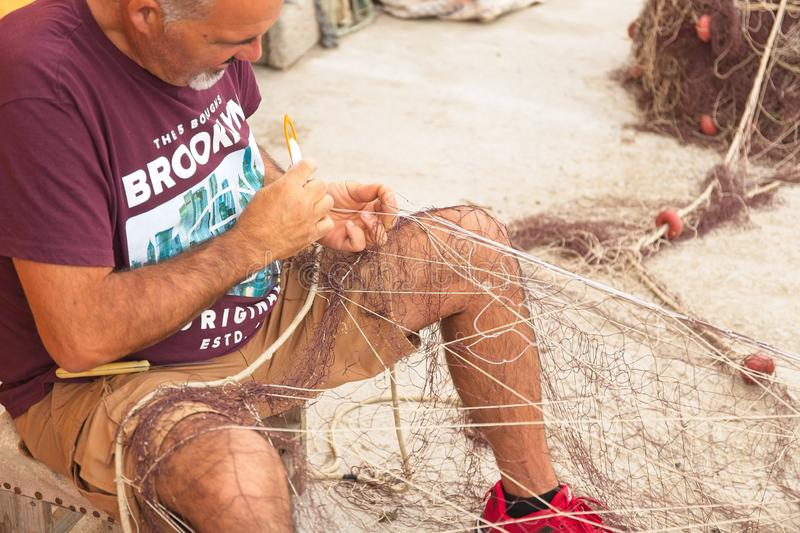 Fisherman sews and patches fishing nets stock photo