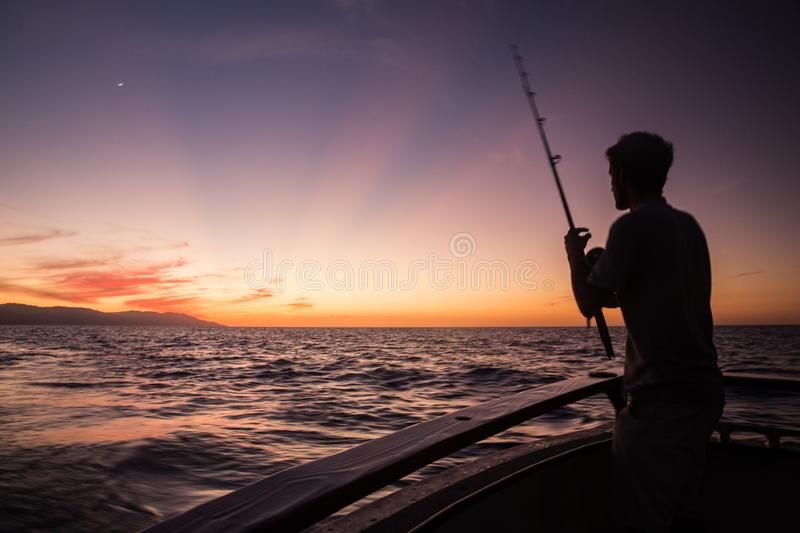 Fisherman Silhouette on Banderas Bay. Fisherman silhouette at sunset on a boat in Puerto, Vallarta, Jalisco, Mexico stock photography