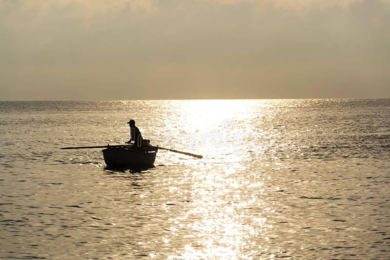 Fisherman silhouette on boat floating against reflecting sunrise, Adriatic Sea royalty free stock images