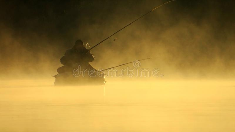 Fisherman silhouette . Foggy autumn morning. stock photography