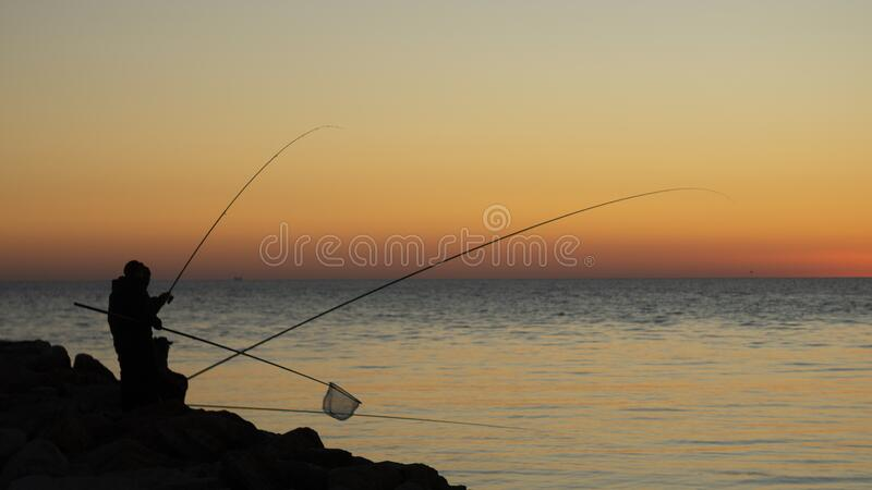 Fisherman silhouette with sunset and Sea as background stock images