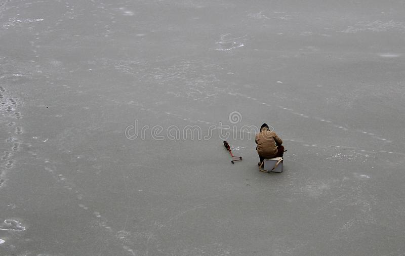 Fisherman sits on the ice and catches fish royalty free stock image