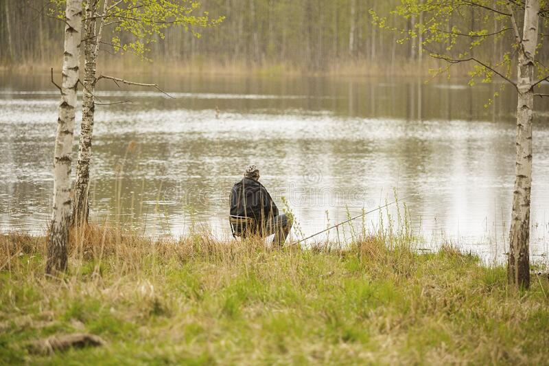 Fisherman sits on the seat on the coast of lake stock images