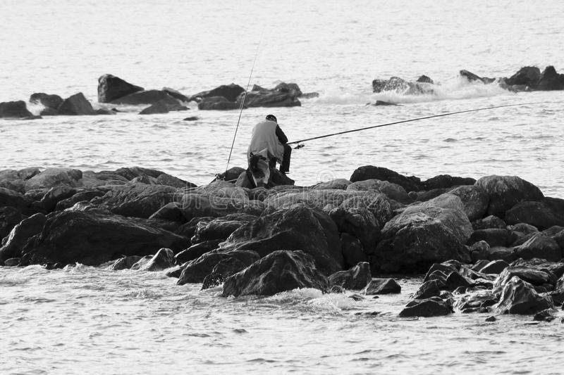 The black and white photo of the fisherman. This fisherman is sitting down on the rockstone. He is fishing for fish. This is a black and white photography stock image