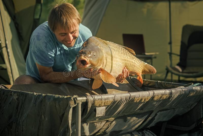 Fisherman smile with carp in fishing camp royalty free stock image