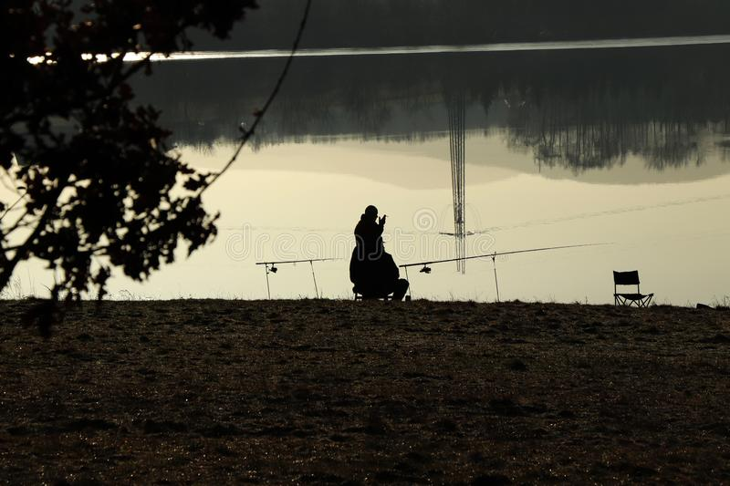 Fisherman smokes a cigarette and talk with his friend while he waits for fish. Dam near Frydek-Mistek in czech republic at sunrise. In backlight. Fishing rods royalty free stock image
