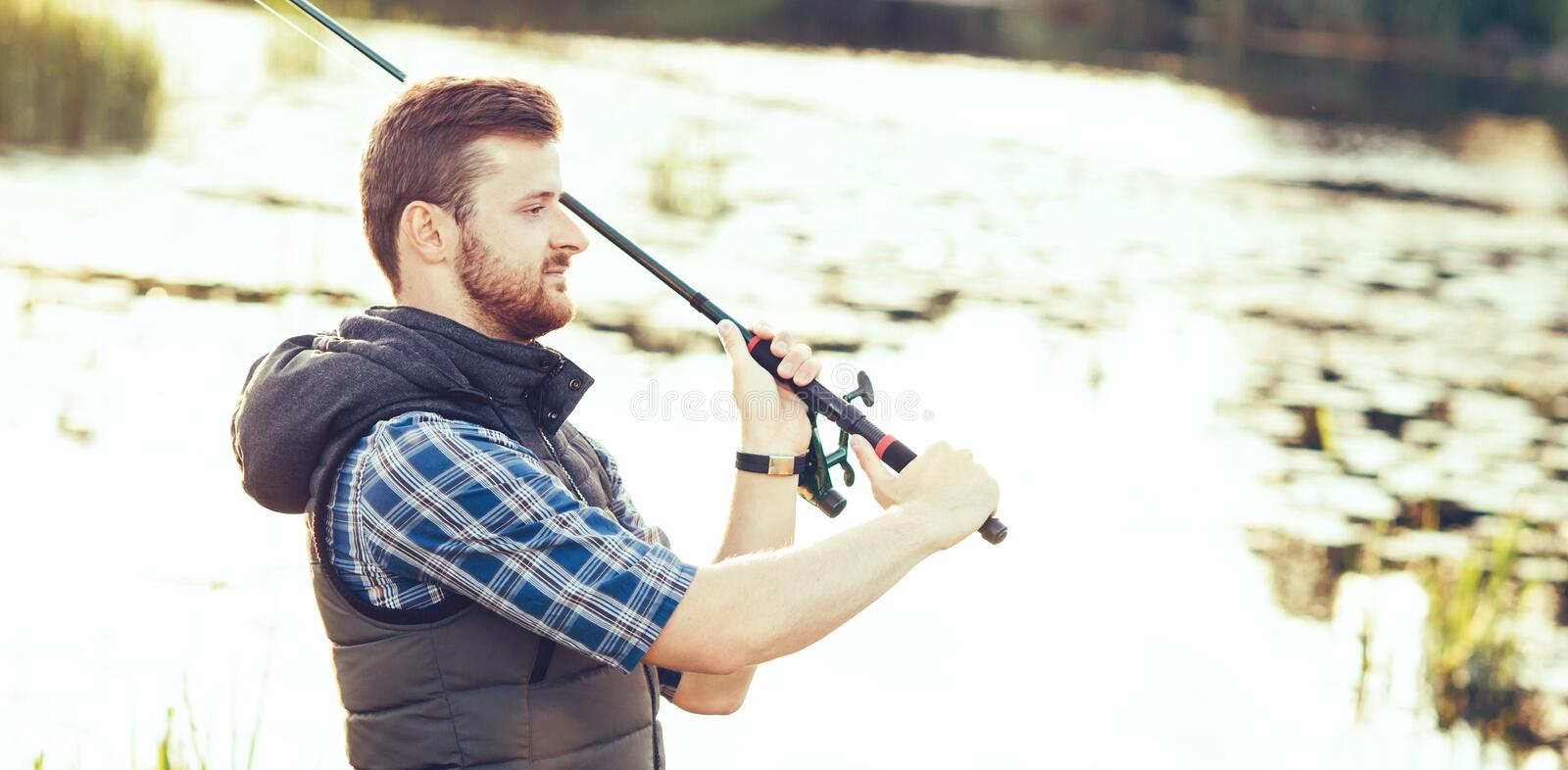 Fisherman with a spinning and bait catching fish on a lake or river. Man on a weekend with a fishing road. Hobby and royalty free stock photography