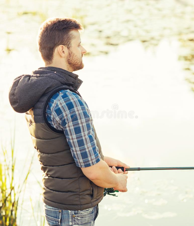 Fisherman with a spinning and bait catching fish on a lake or river. Man on a weekend with a fishing road. Hobby and stock images