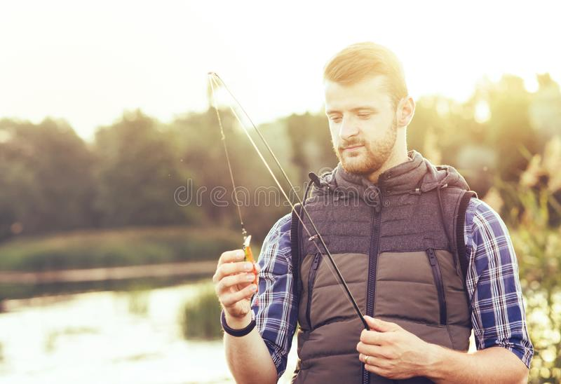 Fisherman with a spinning and bait catching fish on a lake or river. Man on a weekend with a fishing road. Hobby and royalty free stock photos