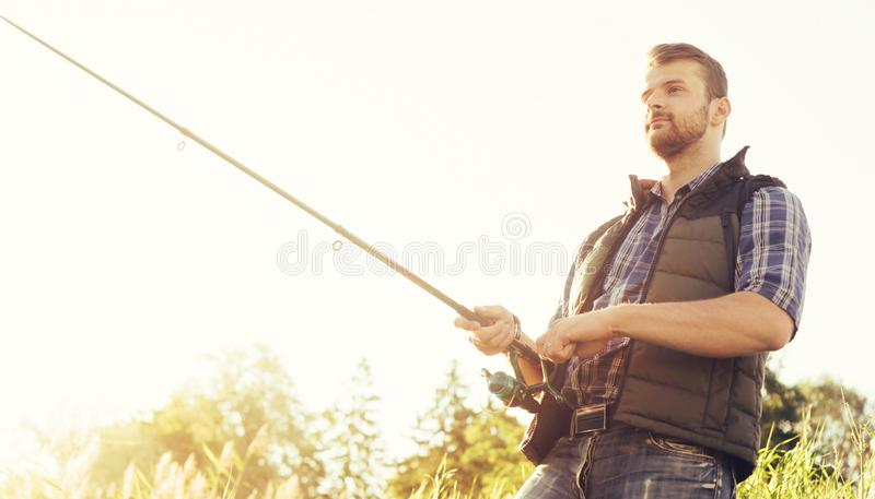 Fisherman with a spinning and bait catching fish on a lake or river. Man on a weekend with a fishing road. Hobby and stock photo