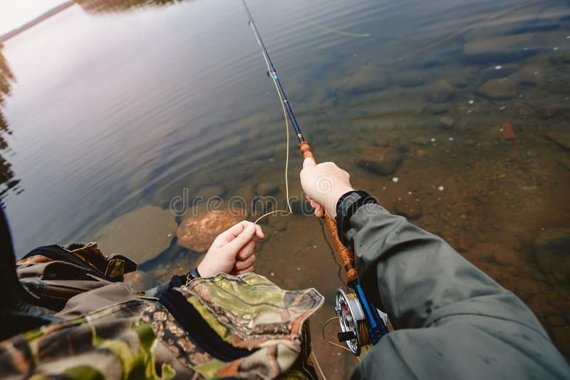 Fisherman spool of rope using rod fly fishing in river, first person view stock photography