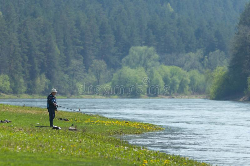 A fisherman standing near the river on the green grass and holding a rod royalty free stock photography