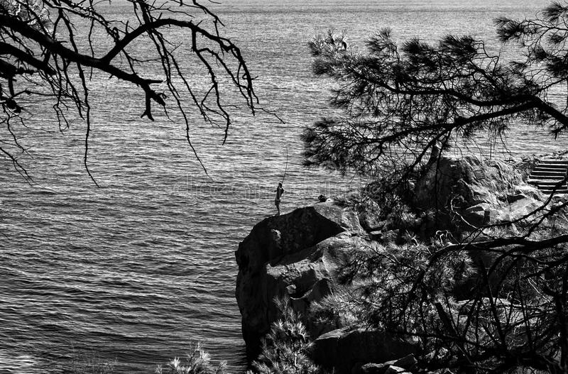 A fisherman stands with a fishing rod on a rock in the sea. Silhouette, bw. stock photos