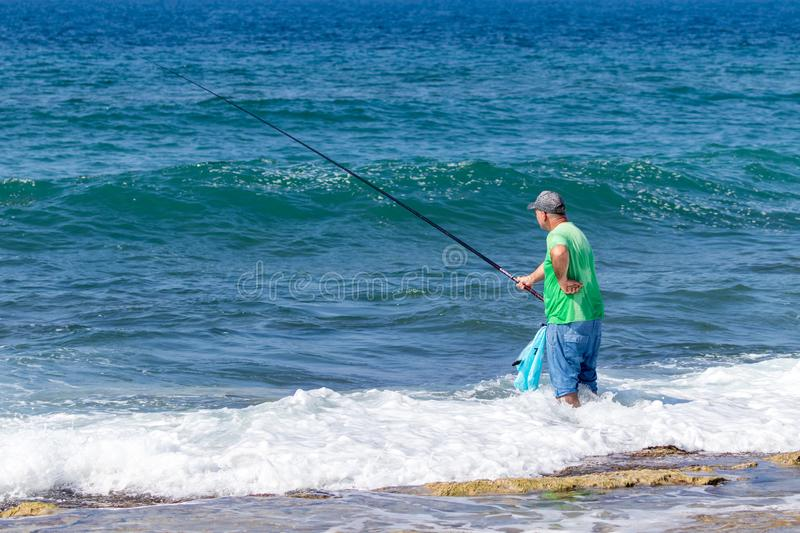 A fisherman stands in the water and fishes with a fishing rod on the Mediterranean coast near the Nahariya city in Israel stock photo
