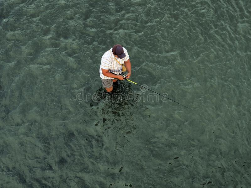 The fisherman stands in the water royalty free stock photos