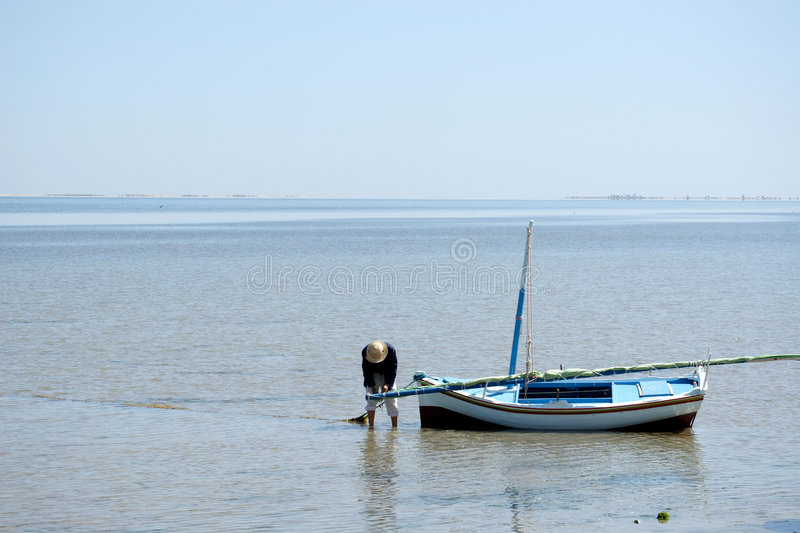 Download Fisherman In Straw Hat Preparing Boat To Sail Out Stock Photo - Image: 690150
