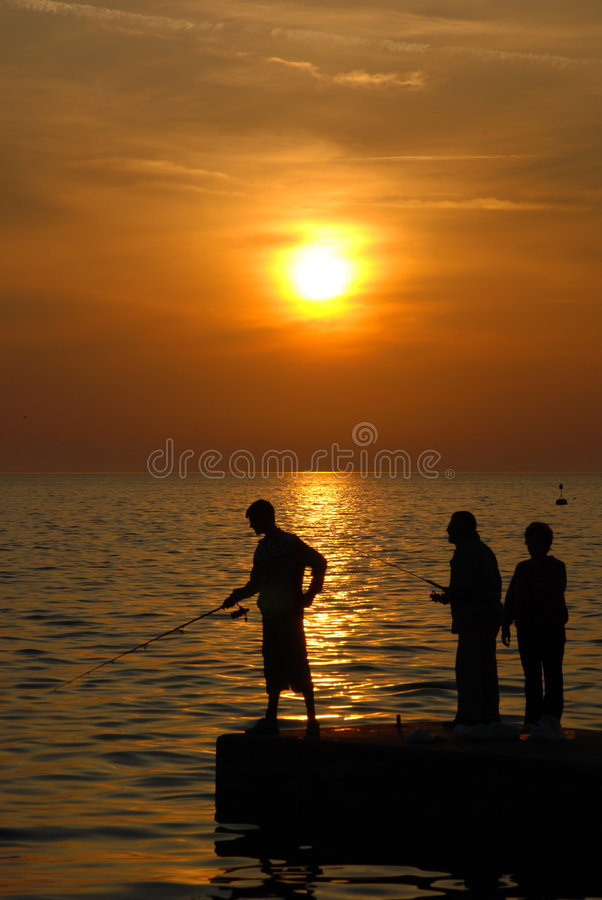 Fisherman sunset. Three Fishermans on a dock during sunset in Pirano (Slovenia royalty free stock photos