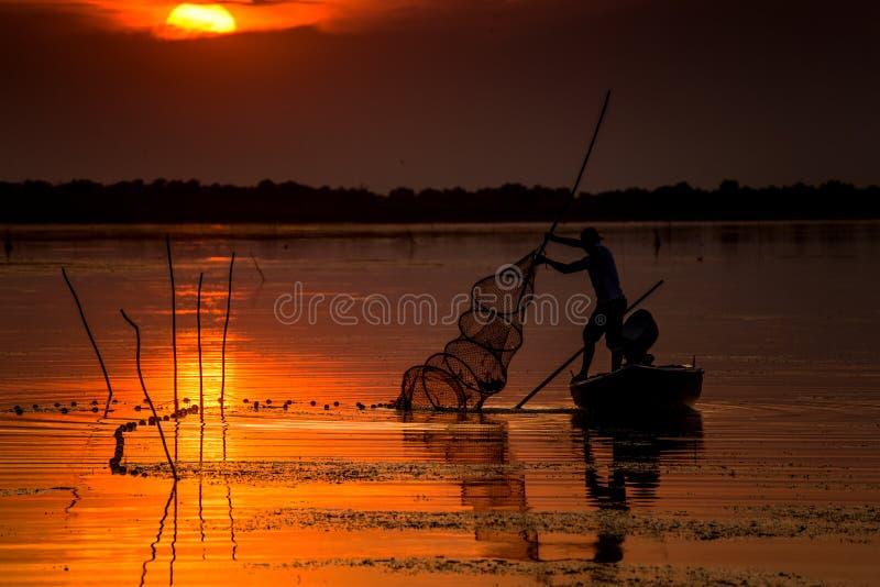 Fisherman at sunset. A fisherman from Danube Delta, checking his fishing nets at sunset royalty free stock photo