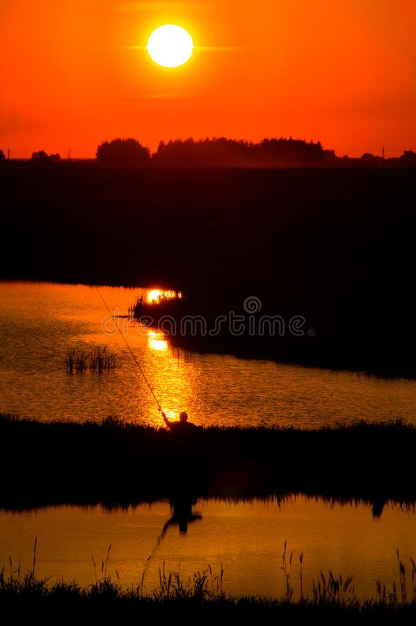Fisherman at sunset on the pond. Fishing in the evening at sunset is the most catching. This shot was made in the Republic of Belarus, where there are many stock image