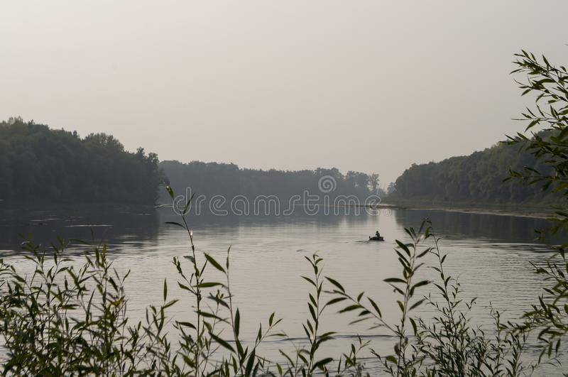 Fisherman are swiming on the boat. Wide river flowing across green forest. Fall. Evening. Reflections of trees in the calm water. stock photos