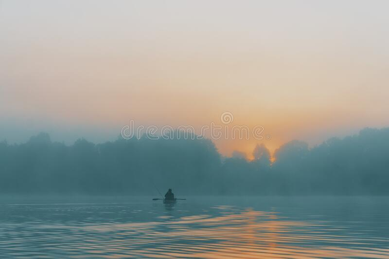 Fisherman swims on a kayak on the river royalty free stock photos