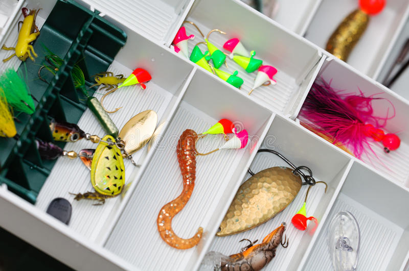 A fisherman tackle box with lures and gear. stock photo